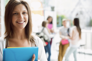 Pretty student smiling and holding notepadsの写真素材 [FYI00003488]