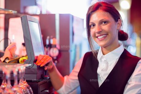 Happy barmaid using touchscreen tillの写真素材 [FYI00003495]