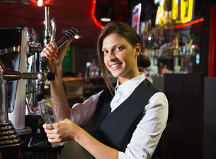 Happy barmaid pulling a pint of beerの写真素材 [FYI00003497]