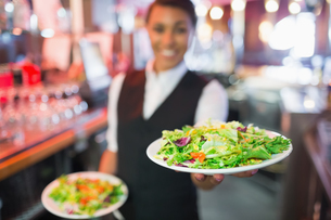 Pretty barmaid holding plates of saladsの素材 [FYI00003498]