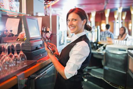 Pretty barmaid using touchscreen tillの写真素材 [FYI00003499]