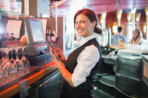 Pretty barmaid using touchscreen tillの写真素材 [FYI00003499]