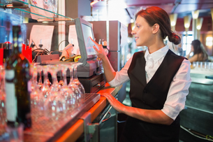 Happy barmaid using touchscreen tillの写真素材 [FYI00003500]