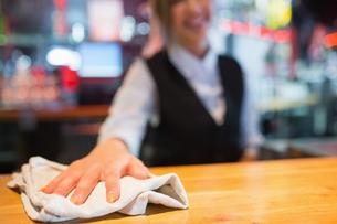 Pretty barmaid wiping down barの写真素材 [FYI00003501]