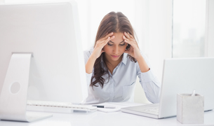 Tired businesswoman sitting at her deskの写真素材 [FYI00003503]