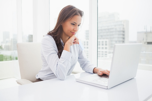 Happy businesswoman using laptop at her deskの写真素材 [FYI00003507]
