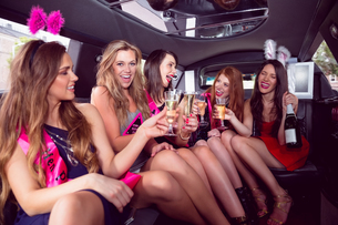 Happy friends drinking champagne in limousineの写真素材 [FYI00003514]