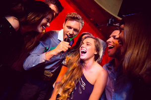 Happy friends singing karaoke togetherの写真素材 [FYI00003515]