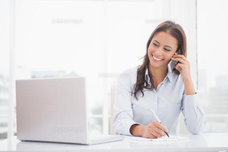 Happy businesswoman using laptop at her deskの写真素材 [FYI00003518]