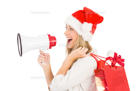 Festive blonde holding megaphone and bagsの素材 [FYI00003523]