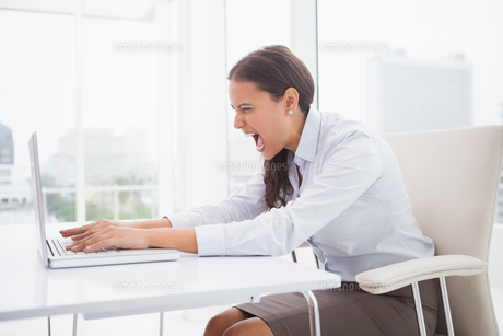 Angry businesswoman using laptop at deskの写真素材 [FYI00003526]