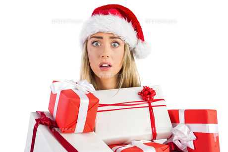Festive blonde holding pile of giftsの写真素材 [FYI00003530]