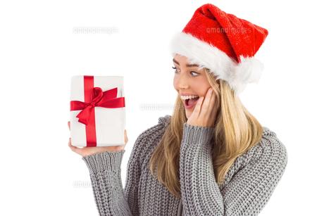 Festive blonde holding christmas giftの写真素材 [FYI00003532]