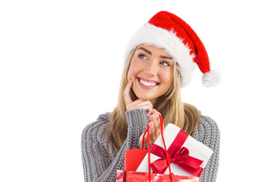 Festive blonde holding christmas gift and bagの写真素材 [FYI00003533]
