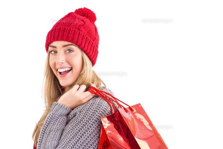 Festive blonde holding shopping bagsの素材 [FYI00003534]
