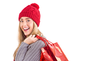 Festive blonde holding shopping bagsの写真素材 [FYI00003534]