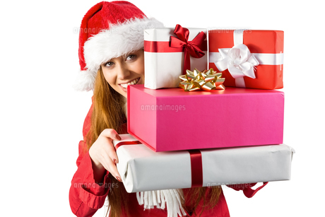Festive redhead holding pile of giftsの写真素材 [FYI00003538]