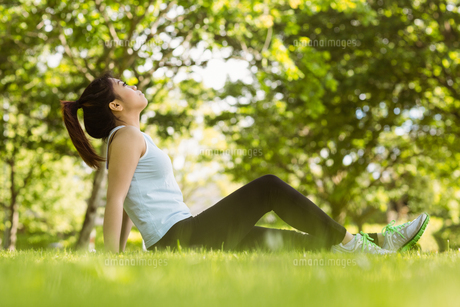 Healthy woman sitting on grass in parkの写真素材 [FYI00003556]