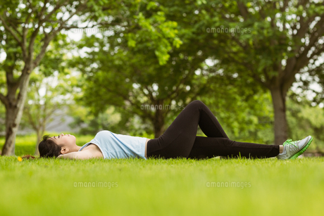 Healthy woman lying on grass in parkの写真素材 [FYI00003557]