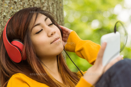 Relaxed woman enjoying music in parkの写真素材 [FYI00003569]