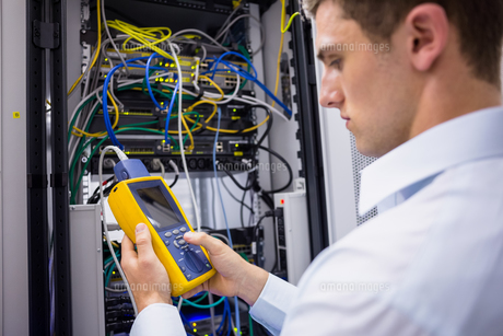 Serious technician using digital cable analyzer on serverの写真素材 [FYI00003591]