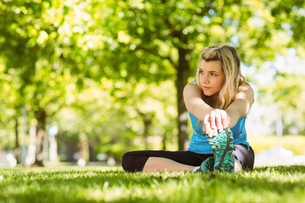 Fit blonde stretching on the grassの写真素材 [FYI00003617]