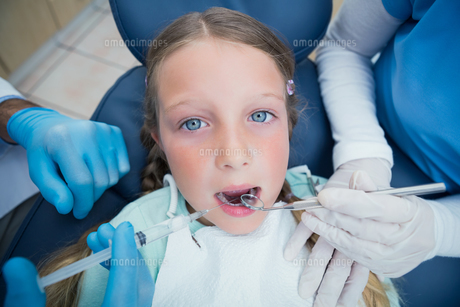 Dentist with assistant examining girls teethの写真素材 [FYI00003638]