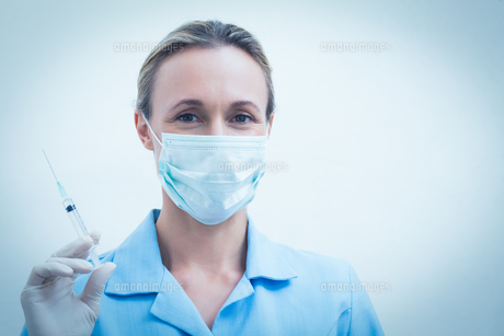 Female dentist in surgical mask holding injectionの写真素材 [FYI00003640]