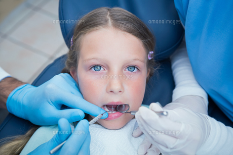 Dentist with assistant examining girls teethの写真素材 [FYI00003644]