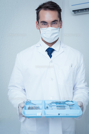 Male dentist in surgical mask holding tray of toolsの写真素材 [FYI00003657]