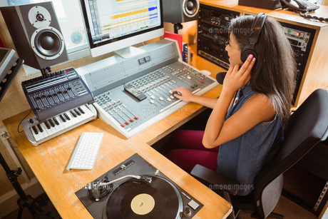 Smiling university student mixing audioの写真素材 [FYI00003689]