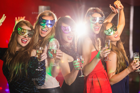 Friends in masquerade masks drinking champagneの写真素材 [FYI00003703]