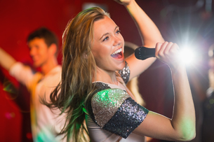 Happy blonde singing karaoke into micの素材 [FYI00003704]