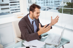 Frustrated businessman using laptop in officeの素材 [FYI00003744]