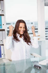 Cheerful businesswoman cheering in officeの写真素材 [FYI00003754]