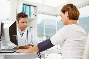 Doctor checking blood pressure of woman at medical officeの写真素材 [FYI00003761]