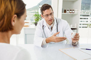 Doctor giving prescription to patient in medical officeの写真素材 [FYI00003762]