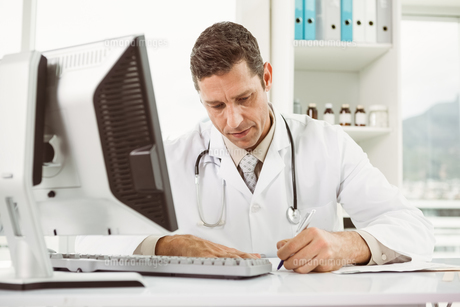 Doctor working at desk in medical officeの写真素材 [FYI00003763]