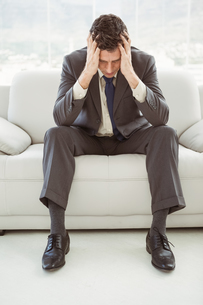 Worried businessman with head in hands sitting on couchの写真素材 [FYI00003764]