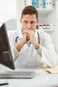 Doctor looking at computer in medical officeの写真素材 [FYI00003765]