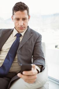 Businessman text messaging in living roomの写真素材 [FYI00003766]