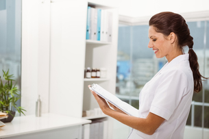 Smiling female doctor holding clipboard in medical officeの写真素材 [FYI00003769]