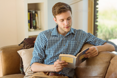 Young man reading on his couchの写真素材 [FYI00003772]