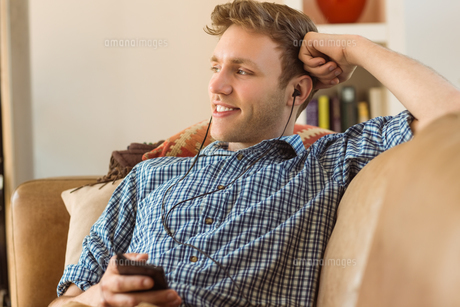 Young man listening to music on his couchの写真素材 [FYI00003775]