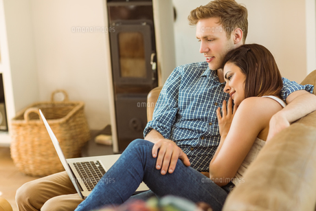 Happy young couple relaxing on the couch with laptopの写真素材 [FYI00003776]