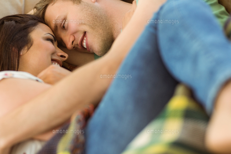 Cute couple cuddling on couchの写真素材 [FYI00003786]