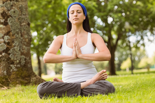 Brunette sitting in lotus pose with hands togetherの素材 [FYI00003807]