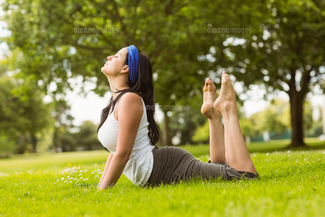 Calm brown hair doing yoga on grassの写真素材 [FYI00003808]