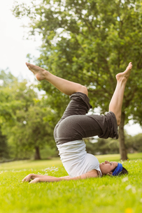 Concentrated brown hair doing yoga on grassの写真素材 [FYI00003811]