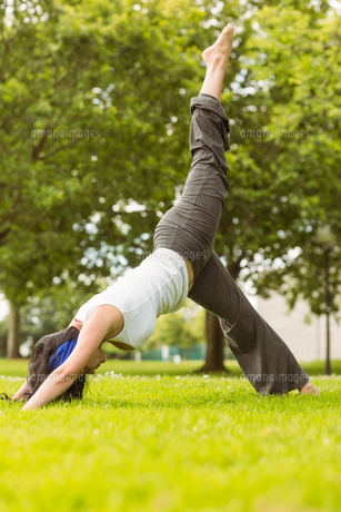Peaceful brown hair doing yoga on grassの写真素材 [FYI00003813]